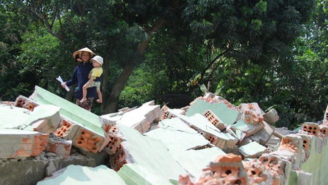 Sau khi đập bỏ nhà cửa, bà Lê Thị Nhàn sống vất vưởng trong lán trại được dựng tạo phía sau lưng